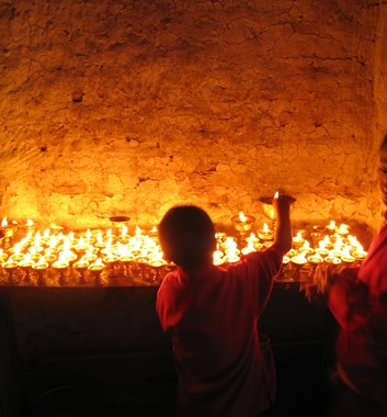 Student buddhist monks light butter lamps in a monastery in Solu Khumbu Nepal